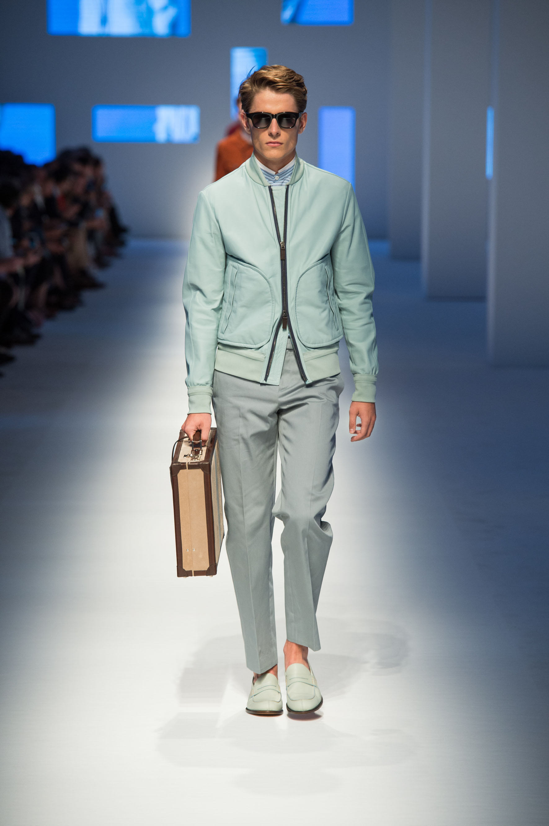 Unlined jacket in rubberized nappa, cotton pants, loafers in calfskin, briefcase with contrast color stripe