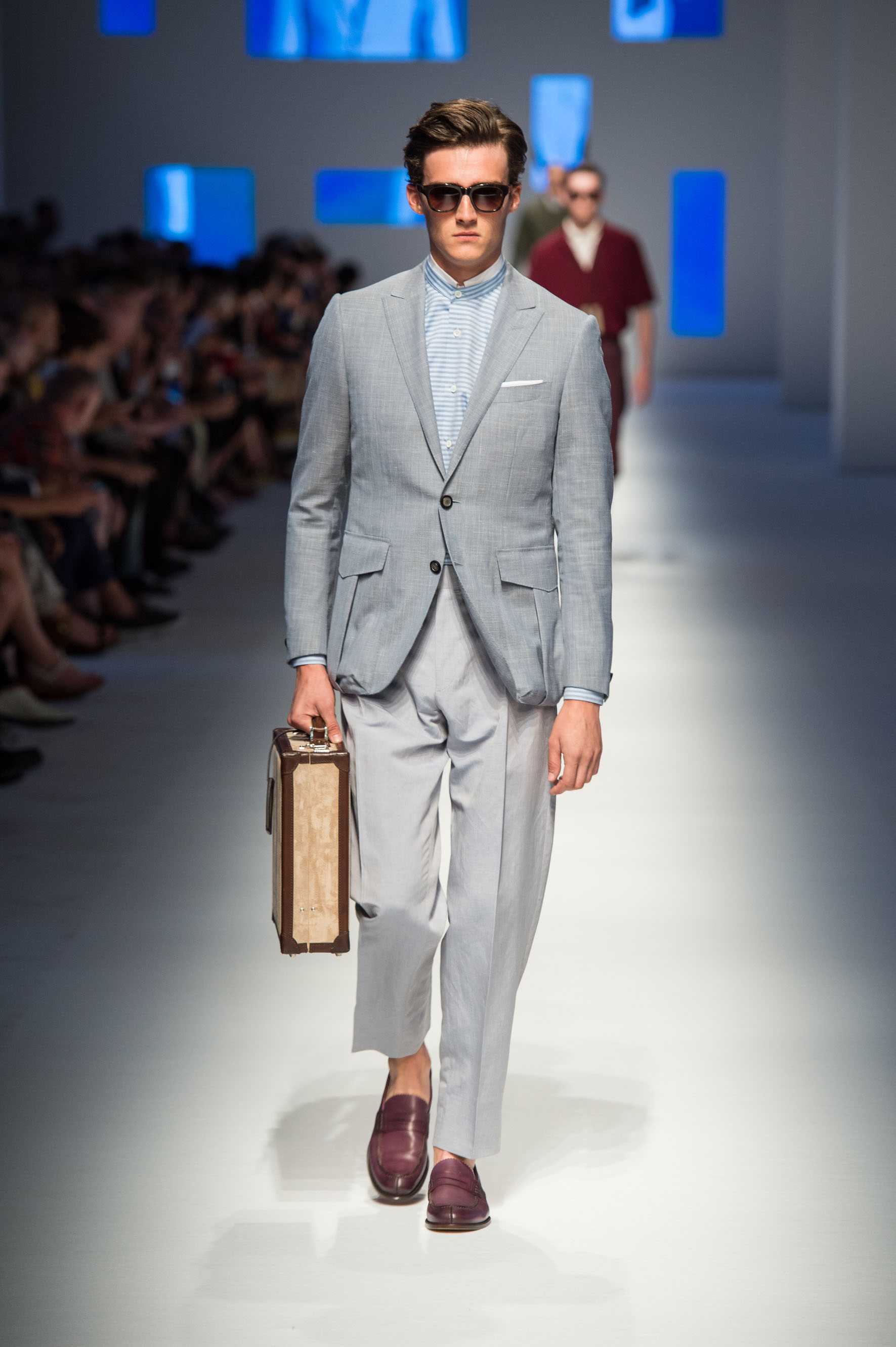 Two-button jacket with flap bellows pockets and martingale in the back, calfskin loafers, briefcase with contrast stripe