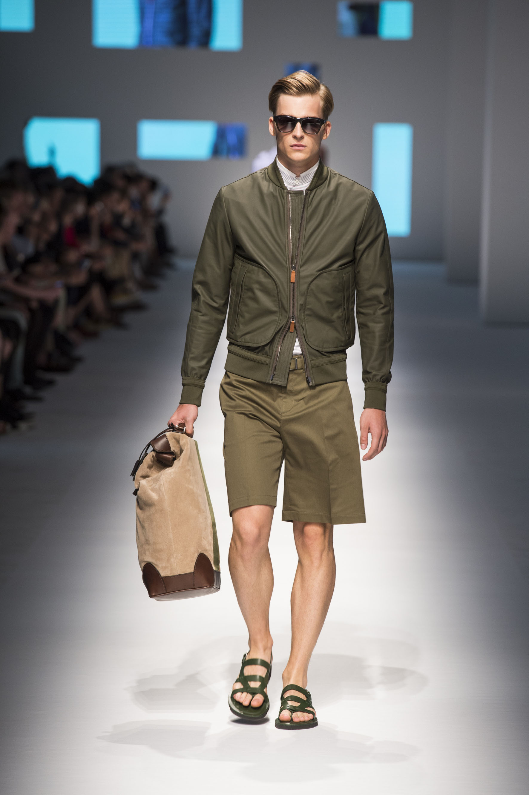 Unlined bomber jacket in rubberized nappa, shorts with removable belt, leather sandals and suede holdall with stripe