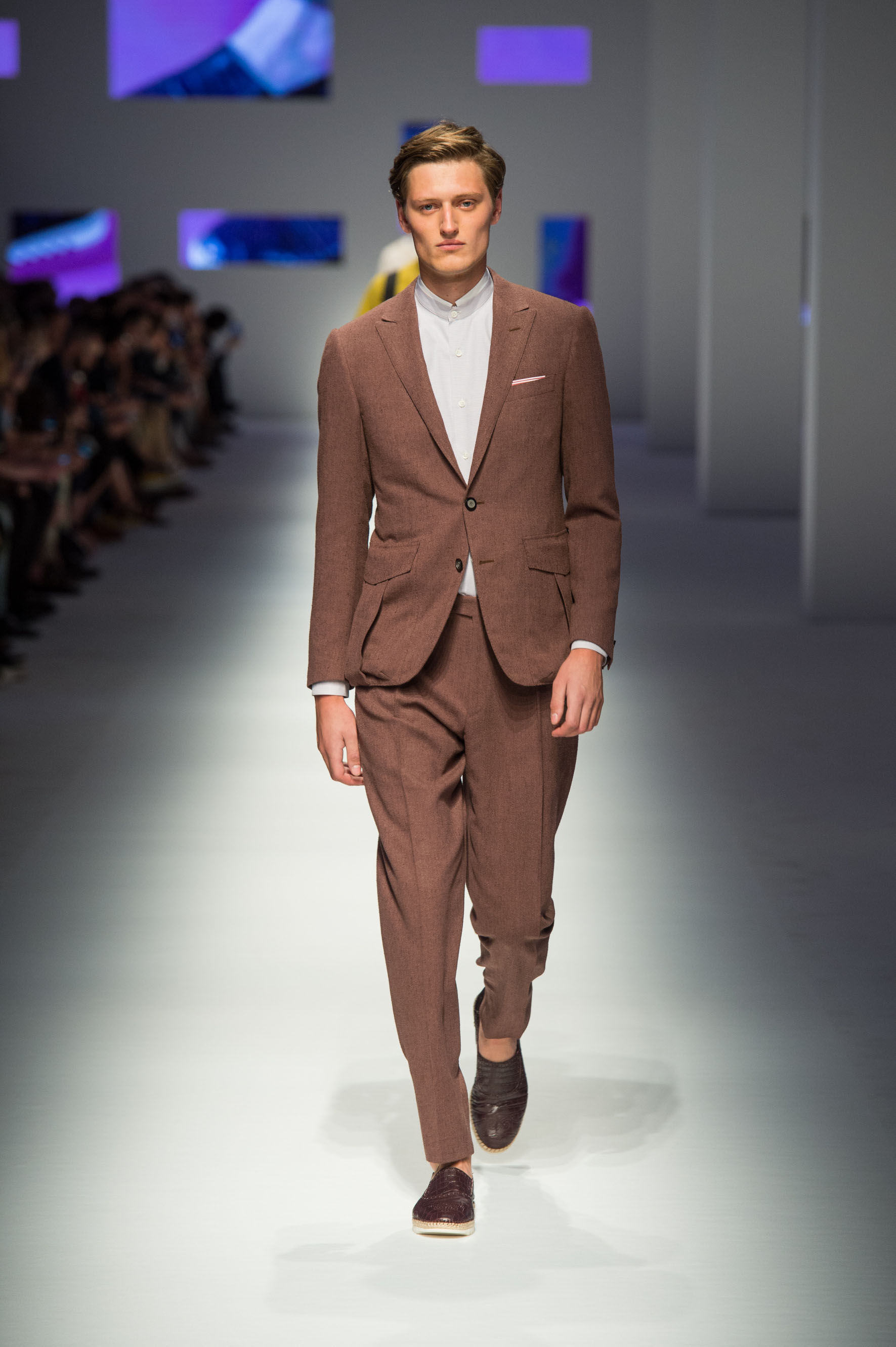 Two-button jacket with martingale and bellow in the back, reverse-pleated pants with terry effect, crocodile loafers